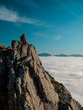Mujer adulta con una mochila que descansa al borde de un acantilado y que mira la salida del sol contra el cielo azul Fotos de archivo