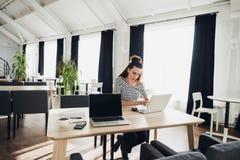 Mujer adulta concentrada que hojea Internet para encontrar la información para el trabajo durante almuerzo Foto de archivo