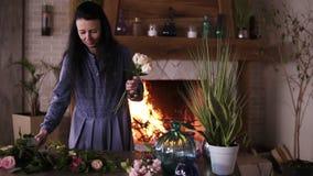 Mujer adulta de pelo largo contratada a comienzo del floristics recoger las mejores flores para su composición de las flores choo almacen de video