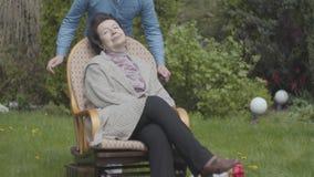 Mujer adulta del retrato que se sienta en el césped en la mecedora que goza del primer del sol Nieto adulto que cubre ojos del almacen de metraje de vídeo