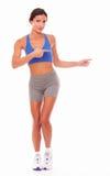 Mujer adulta deportiva que señala en su izquierda Imagenes de archivo