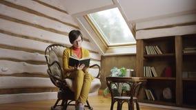 Mujer adulta en libro de lectura de los vidrios en ático almacen de video