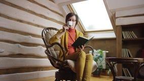 Mujer adulta en libro de lectura de los vidrios mientras que bebe el café en ático almacen de video