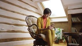 Mujer adulta en los vidrios que mandan un SMS en smartphone en ático almacen de metraje de vídeo