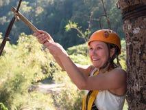 Mujer adulta en un casco y con una cara asustada que se aferra a un cable del hierro antes de saltar Imagenes de archivo
