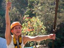 Mujer adulta en un casco y con una expresión sorprendida en su cara que se aferra a un cable de acero Fotografía de archivo