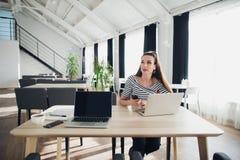 Mujer adulta en un escritorio de oficina moderno, trabajando en el ordenador portátil y el teléfono, mirando lejos, pensando en p foto de archivo