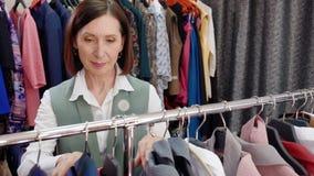 Mujer adulta feliz que elige la ropa mientras que hace compras en boutique elegante Mujer madura alegre que mira la nueva ropa metrajes
