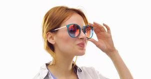 Mujer adulta fresca de la diversión del pelo joven feliz hermoso del pelirrojo que sonríe y que usa las gafas de sol Acción de la almacen de video