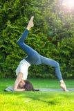Mujer adulta hermosa que hace yoga en la mañana del verano Imagenes de archivo
