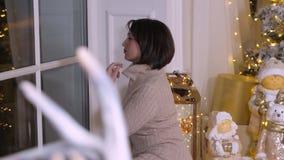 Mujer adulta hermosa que se sienta cerca de ventana en la Nochebuena en sala de estar acogedora metrajes