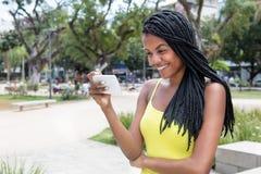 Mujer adulta joven afroamericana que ve la TV con el teléfono Fotos de archivo