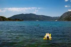 Mujer adulta joven en el colchón amarillo en agua de mar azul fotos de archivo libres de regalías