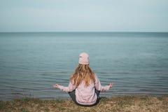 Mujer adulta joven en el sombrero rosado que se sienta solamente en los pe?ascos, mirada del mar, concepto de la libertad, atm?sf imagen de archivo