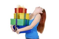 Mujer adulta joven en la ropa casual que sostiene o que lleva la pequeña pila de presentes de la Navidad o de cumpleaños Fotografía de archivo