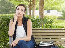 Mujer adulta joven melancólica que se sienta en banco al lado de los libros Foto de archivo