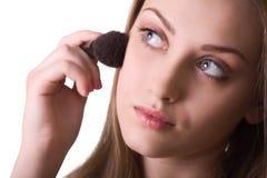 Mujer adulta joven que aplica blusher Imágenes de archivo libres de regalías