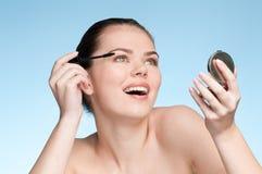Mujer adulta joven que aplica el cepillo cosmético del rimel Fotografía de archivo