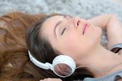 Mujer adulta joven que miente en el piso que escucha la música Imagen de archivo