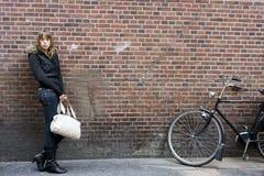 Mujer adulta joven que se coloca con el monedero a disposición Foto de archivo