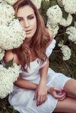 Mujer adulta joven que se sienta cerca de muchas flores en parque Imágenes de archivo libres de regalías
