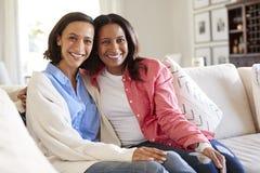 Mujer adulta joven que se sienta en el sofá en sala de estar con su madre que sonríe a la cámara fotografía de archivo libre de regalías