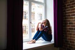 Mujer adulta joven triste que se sienta en una ventana Foto de archivo libre de regalías
