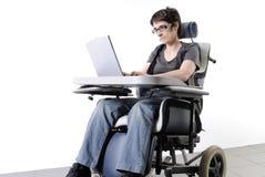 Mujer adulta lisiada con la computadora portátil en un sillón de ruedas Foto de archivo libre de regalías