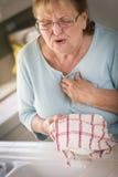 Mujer adulta mayor en el fregadero con dolores de pecho Fotografía de archivo libre de regalías