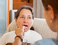 Mujer adulta que da el jarabe a la madre madura Imagen de archivo libre de regalías