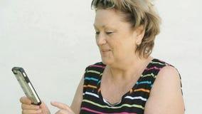 Mujer adulta que habla con el marido que usa el teléfono elegante almacen de metraje de vídeo