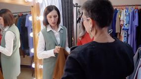 Mujer adulta que intenta a nuevos amigos de la ropa juntos en tienda de ropa Consultor femenino que da consejo al rato de la muje metrajes