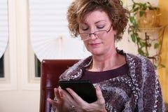 Mujer adulta que lee una tableta Fotos de archivo