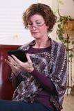 Mujer adulta que lee una tableta Foto de archivo libre de regalías