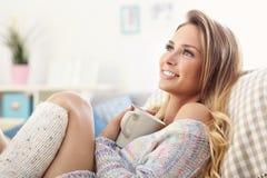 Mujer adulta que se sienta en el sofá con café fotos de archivo