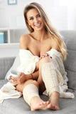 Mujer adulta que se sienta en el sofá con café imagen de archivo
