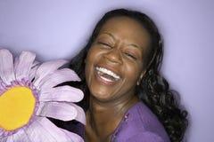 Mujer adulta que sostiene la flor falsa púrpura grande. imagen de archivo