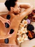 Mujer adulta que tiene masaje de piedra caliente en salón del balneario fotografía de archivo libre de regalías