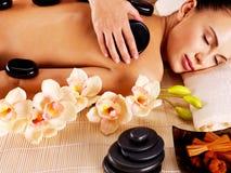 Mujer adulta que tiene masaje de piedra caliente en salón del balneario Foto de archivo