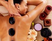 Mujer adulta que tiene masaje de piedra caliente en salón del balneario Imagen de archivo libre de regalías