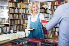 Mujer adulta que toma el libro y que habla con el vendedor foto de archivo libre de regalías