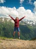 Mujer adulta saltada para arriba y gritos contra el contexto de las montañas Foto de archivo