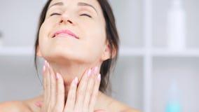Mujer adulta sonriente atractiva que aplica la crema antienvejecedora en cuello y el contorno del primer de la barbilla almacen de video