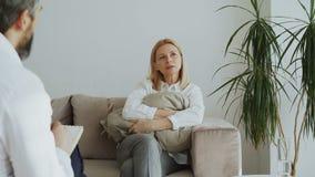 Mujer adulta trastornada que sostiene la almohada y que habla de sus problemas con el psicoanalista de sexo masculino en su ofici almacen de metraje de vídeo
