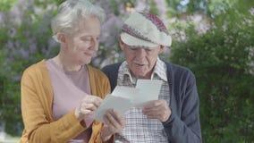 Mujer adulta y hombre del retrato que miran las fotos viejas que recuerdan momentos felices sentarse en un banco en el parque Par almacen de metraje de vídeo