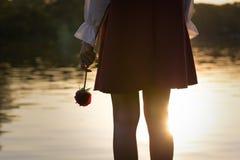 Mujer afligida que sostiene una rosa Fotos de archivo