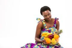 Mujer africana bastante feliz que sienta y que mira las frutas frescas Foto de archivo