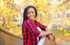 Mujer africana bastante sonriente del retrato que lleva una camisa a cuadros roja en otoño soleado Imágenes de archivo libres de regalías