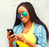 Mujer africana bastante sonriente que usa smartphone Imágenes de archivo libres de regalías