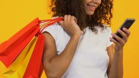Mujer africana bonita que usa el app del smartphone, sosteniendo bolsos de la compra, pago en línea almacen de video